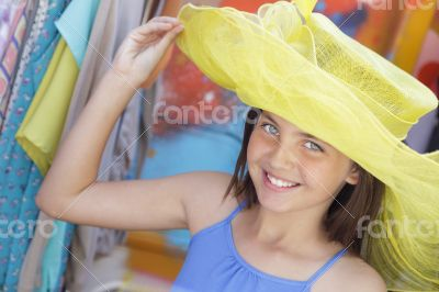 Pretty Girl Tries on Yellow Hat at Market