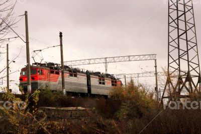 Electic train running by the rails on the fields
