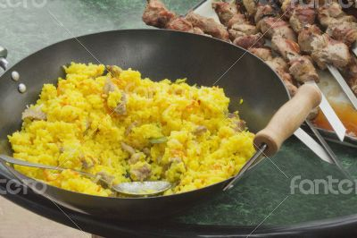 Pilaf in a large frying pan and grilled kebabs.