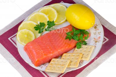 Salmon fillet and lemons on a platter on a white background.