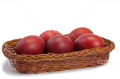 Red Easter eggs in a basket on a white background.