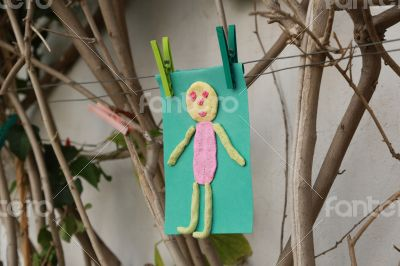Child`s handmade small man on a green color paper