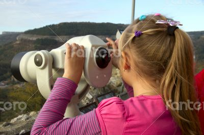 Girl looks into the distance through a telescope
