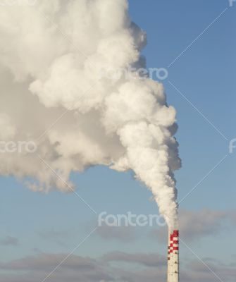 Smokestacks with white steam in the blue sky.