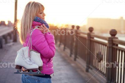 Beautiful young blond woman walking on bridge
