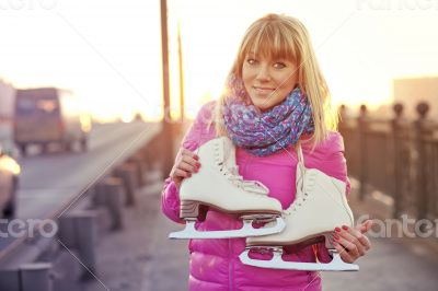 Beautiful smiling blond woman with ice skates