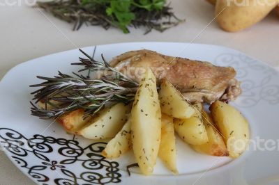 Baked potatoes and chicken with rosemary