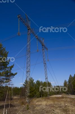 High voltage power lines against the blue sky and the spring for