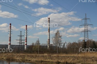 Factory pipes and high voltage power lines against the blue sky
