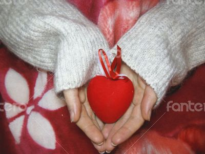 Valentine heart and heart shape candle in woman hands