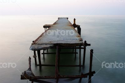 Abandoned concrete wharf in sea within sunrise