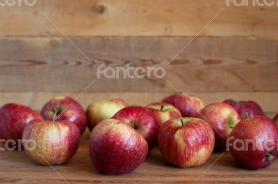 Red apples lie on a wooden surface