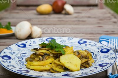 Baked potatoes with mushrooms and parsley on the white blue plat