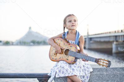 Girl playing guitar on river embankment