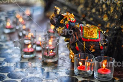 Candles with an elephant sculpture sacrifice