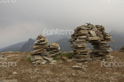 Few flat stones stacked pyramid atop a mountain on the backgroun