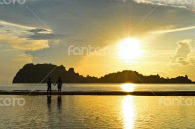 Two children on the beach watching the sunrise