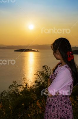 Young woman watching the sunset over the lake