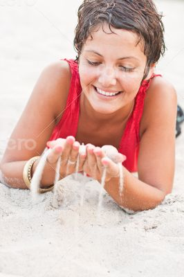 brunet woman in red lying on a sand