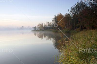 Foggy morning landscape in the autumn park near the lake. Vintag