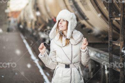 Pretty girl in winter blizzard on railroad station