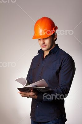 Builder in protective helmet reading papers