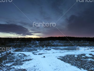 Snow covered stone quarry in the winter with all the tools and b