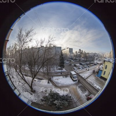 A view from the window on the winter city and houses  by fisheye view