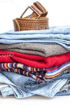 Pile of woolen jumpers and blue jeans