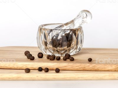Black pepper in a transparent mortar with a pestle