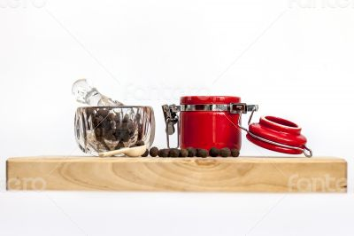 Black pepper in a transparent mortar and container for spices