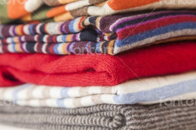 Pile of woolen jumpers of various colors