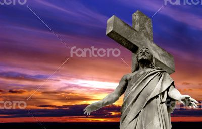 crucified Jesus Christ against dramatic sunset