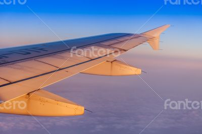 Flight at sunrise. The wing of the plane