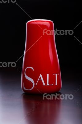 Red salt-cellar, pepper-box on dark background