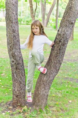 Cute girl in summer sit on tree