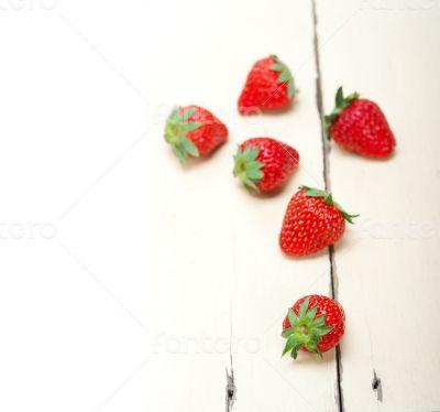 fresh organic strawberry over white wood