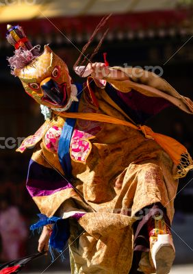 Buddhist monk in mask performs religious dancе