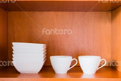 Organized minimalistic kitchen cabinet with white porcelain bowl