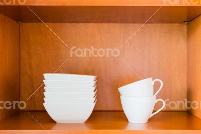 Organized minimalistic kitchen cabinet with white porcelain bowl