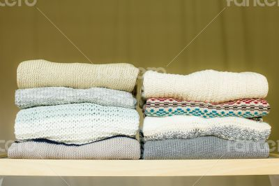 Pile of warm sweaters on a shelf
