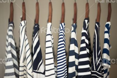 A row of navy striped tops for women on wooden hangers in a clos