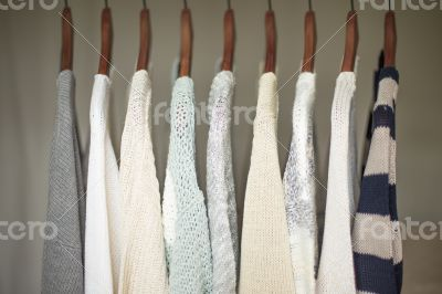 A row of warm and soft sweaters for women on wooden hangers in a