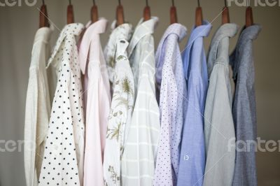 Assorted business shirts on hangers in a closet