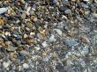 Wet brilliant pebble and sea wave